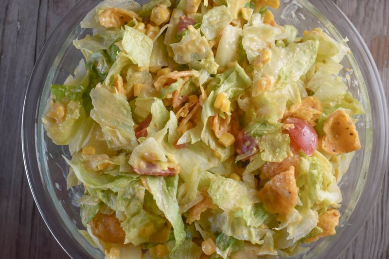 Cheesy Frito Salad is an easy side dish option with corn chips and a melted Velveeta dressing.