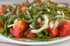 Italian Green Bean Salad is a cold salad featuring thin style green beans, tomatoes and onions tossed in a tasty vinaigrette. A healthy sprinkling of Parmesan cheese takes this salad from good to great. Serve along side grilled chicken for the perfect meal.