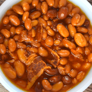 Crock Pot Baked Beans with Bacon is an easy recipe to throw together for your next party.  A combination of canned beans are bathed in a sweet brown sugar and ketchup based sauce that will compliment any entree.