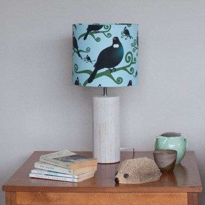 Tui table lamp on a coffee table with books and tea.