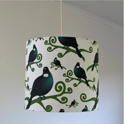 A lampshade featuring a design of many tui on a white background.