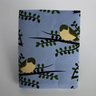 Product photograph showing the front of the visual diary cover. The fabric features a repeat illustration of a tauhou bird sitting on a kōwhai branch.