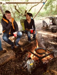 two adults cooking beans on campfire