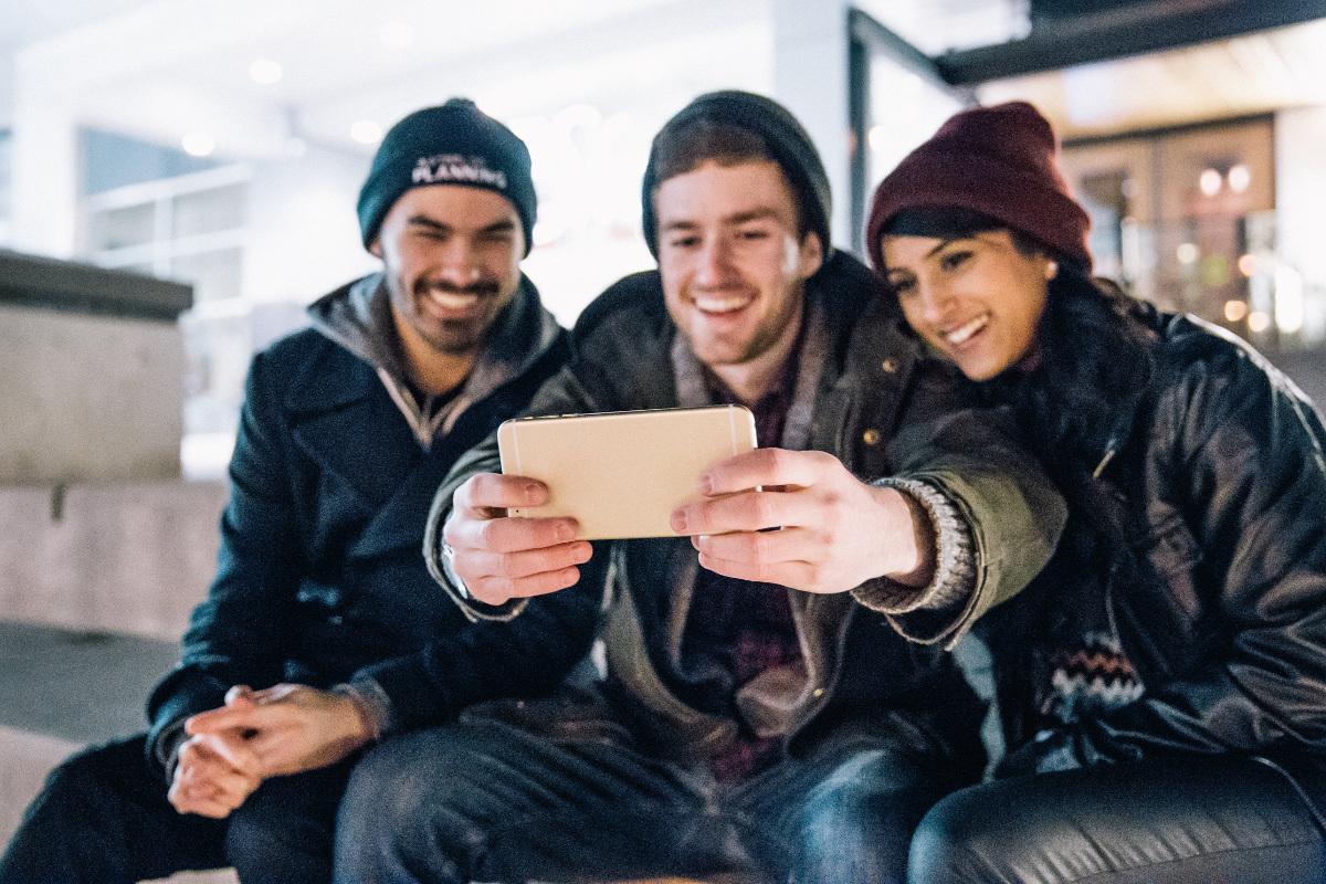 A trio of people having a selfie.