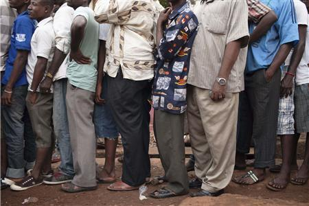 Men queue to vote during presidential elections in Freetown
