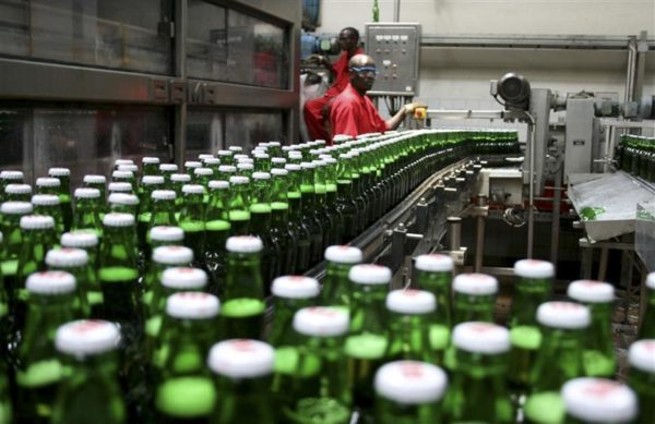 Technicians inspect beer bottles on a conveyor belt in a brewery in Gisneyi