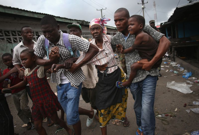 MONROVIA, LIBERIA - AUGUST 20:  Family members of West Point district commissioner Miata Flowers flee the slum while being escorted by the Ebola Task Force on August 20, 2014 in Monrovia, Liberia. The military was called in to extract the commissioner and her family members from the seaside twon after residents blamed the government for setting up a holding center for suspected Ebola patients in their community. A mob overran and closed the facility on August 16. The military also began enforcing a quarrantine on West Point, a congested slum of 75,000, fearing a spread of the epidemic. The Ebola virus has killed more than 1,200 people in four African nations, more in Liberia than any other country.  (Photo by John Moore/Getty Images)