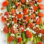 asparagus tomatoes and feta cheese on a white plate