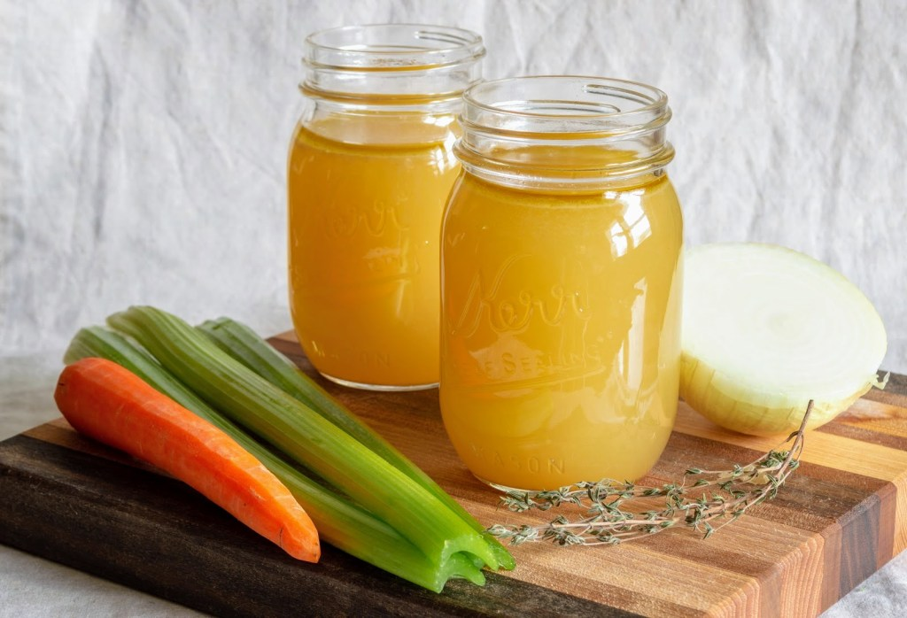 stock in glass jar sitting on wooden cutting board with vegetables