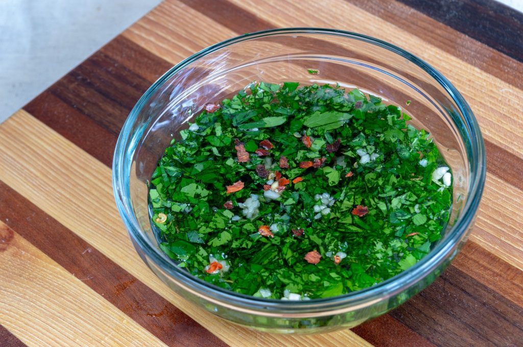 glass bowl of chimichurri on a wooden cutting board