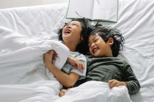 kids laughing on bed