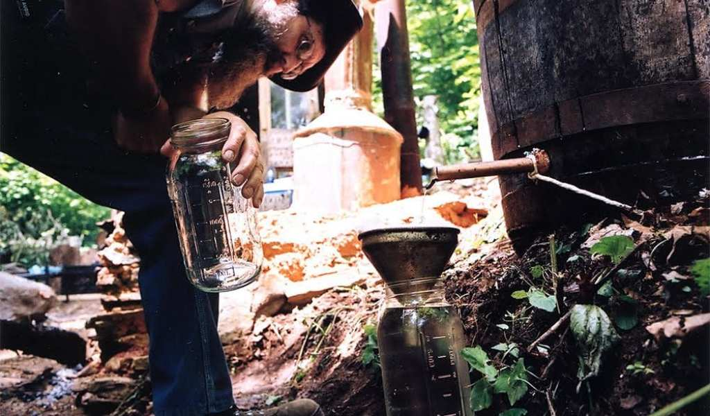 """Popcorn Sutton's partner JB siphons the shine at an undisclosed location in the mountains of East Tennessee during the filming of the """"Last Dam Run"""" documentary (photo courtesy of Sucker Punch Pictures)"""