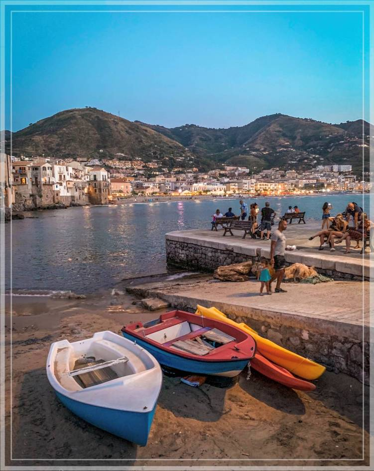 Colorful boats at a beach in Cefalu at sunset