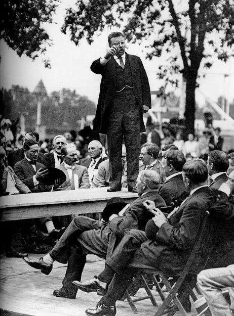 Teddy Roosevelt delivers a speech on a platform.
