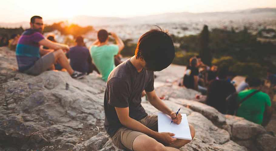 person holding a pen, writing on a paper while sitting on the rock formation