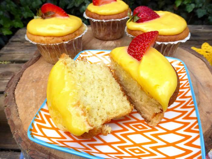 picture of a sliced in two lemon curd cupcake with a strawberry on top