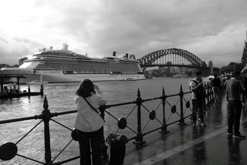 A cruise ship moored near the Sydney Harbour Bridge is being photographed by a tourist