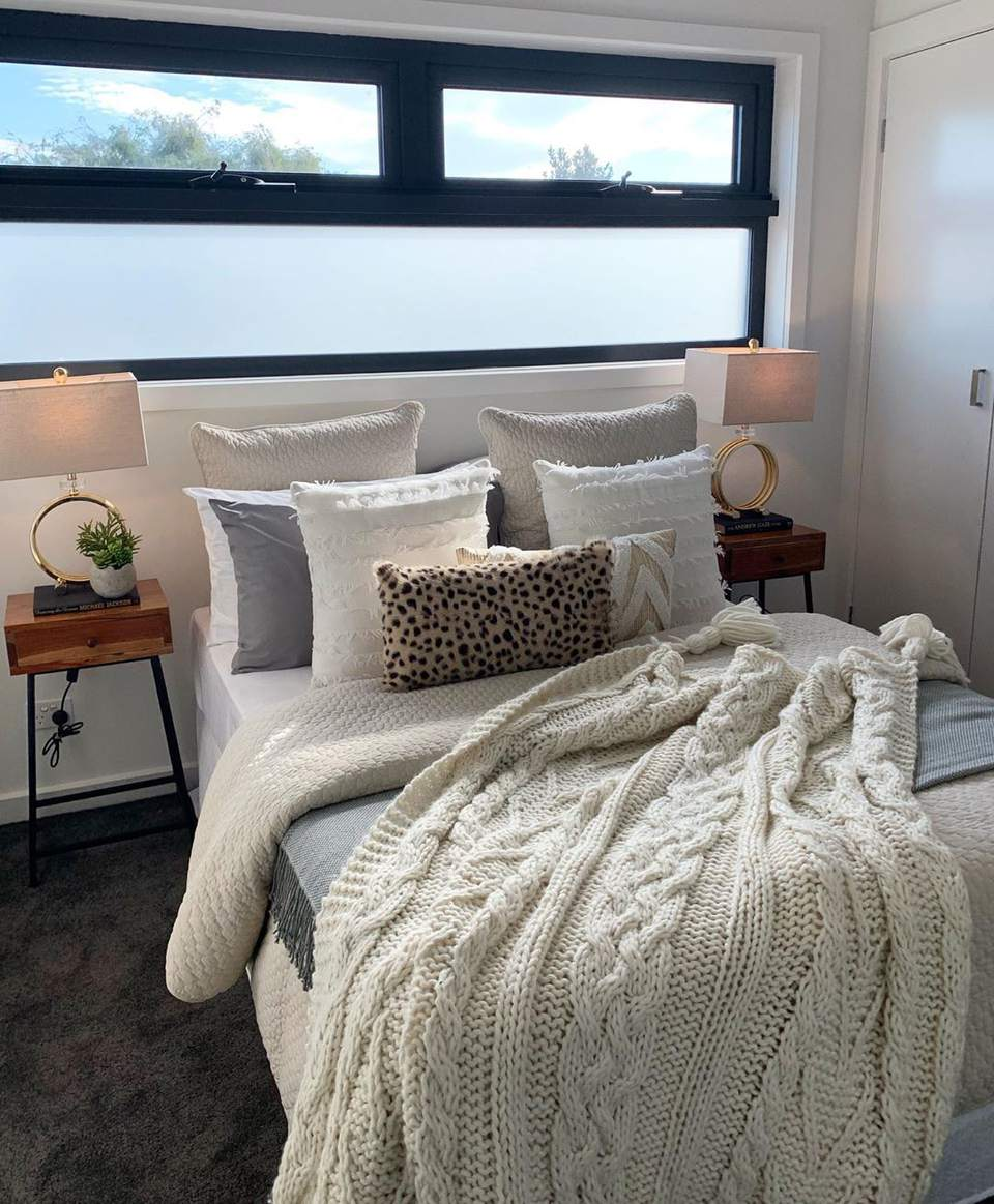 A bed with white blankets under a wide window