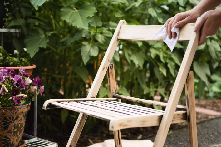 Lint-free cloth wiping down excess sanding dust from wooden chair