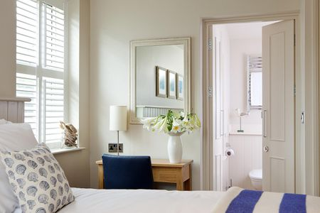 8 Easy Ways to Make a Small Room Look Larger Bright bedroom with mirror and flowers