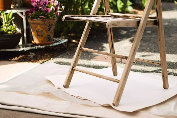 Large paper and plastic sheets under wooden chair