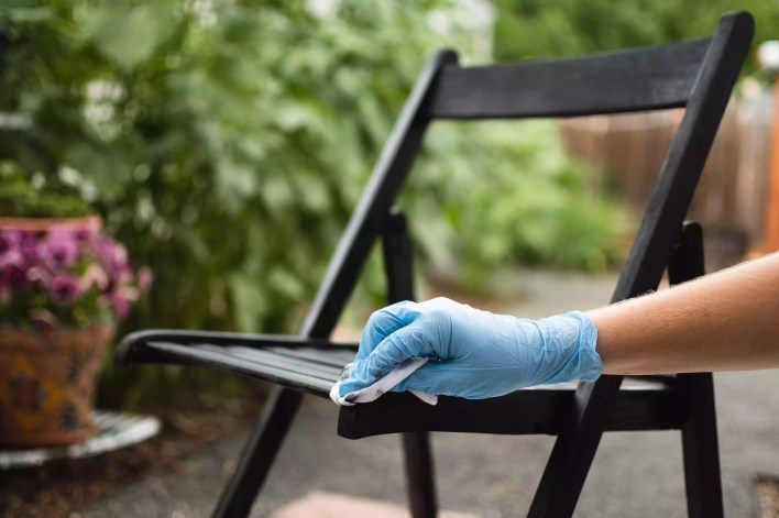 Lint-free rag removing excess black stain on wooden chair while wearing blue gloves