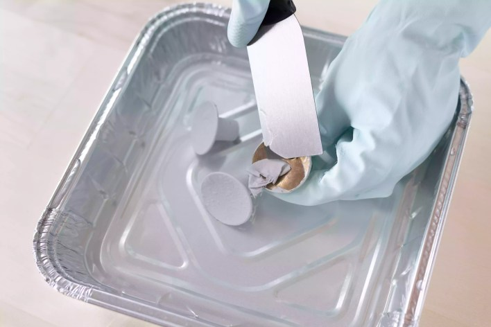 Paint being scraped off metal knobs in water with paint scraper and gloves
