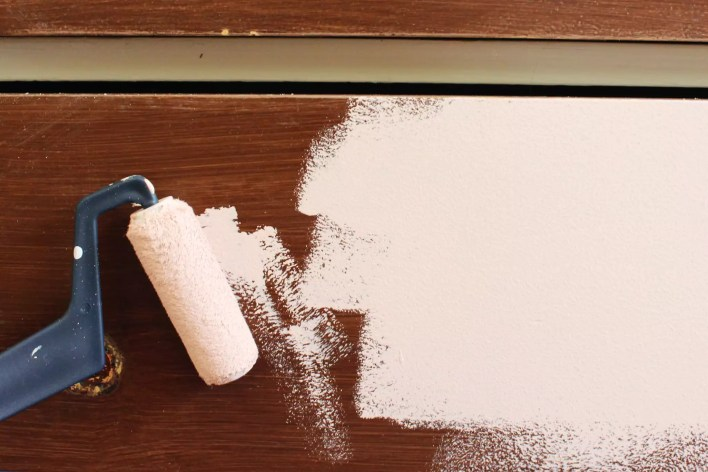 Using a roller brush with chalk paint on a dresser