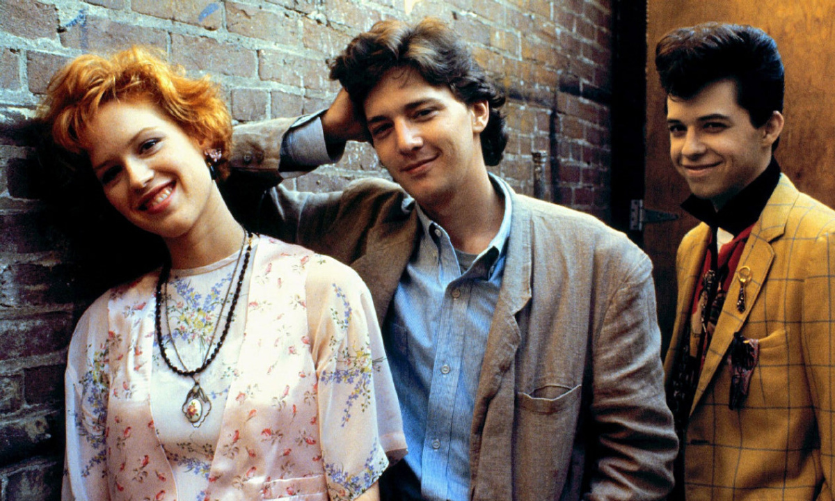 Molly Ringwald, Andrew McCarthy and Jon Cryer in a promotional still from Pretty in Pink (1986). L-R: three teenagers, Andie, a smiling white girl with short, curly red hair wearing a white dress with small blue flowers, Blane, a white boy wearing a pale blue shirt and a beige jacket over it leaning casually on the wall behind them, and finally Duckie, a quirky white boy with quiffed black hair and a yellow checked suit jacket and his black shirt collar popped, giving a cheeky smile to the camera.