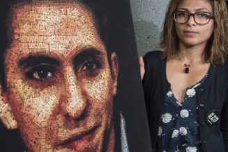 Ensaf Haidar, wife of Raif Badawi, stands next to a poster of a book of articles written by the imprisoned Saudi blogger, Tuesday, June 16, 2015 in Montreal. Badawi, who is imprisoned for criticizing Islam on his blog, is currently serving a 10-year prison sentence and is also supposed to receive 1,000 lashes delivered in batches of 50 over 20 weeks.