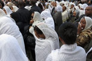 Mourners from the Eritrean community weep outside the funeral of civic leader Nahom Tsehaie Berhane, who was stabbed to death last week.