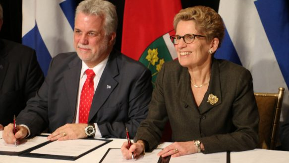 Quebec Premier Philippe Couillard, left, and Ontario Premier Kathleen Wynne sign a memorandum of agreement, one of four inked after a daylong Ontario-Quebec joint cabinet meetings held at the Fairmont Royal York Hotel in Toronto on Friday.