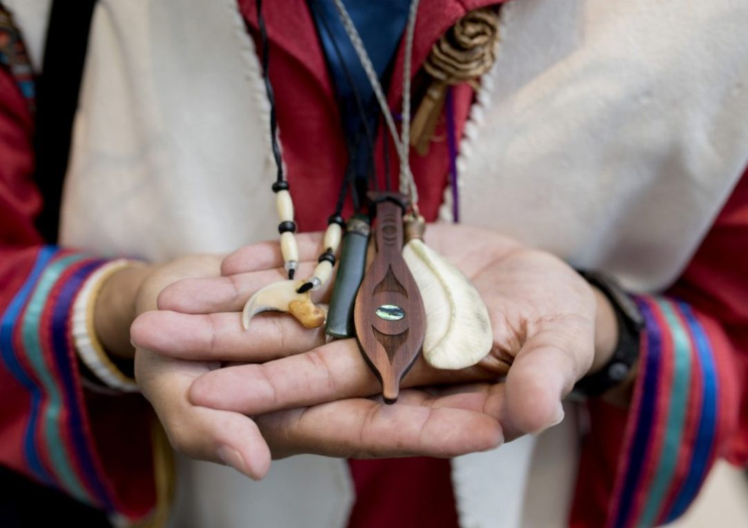Terry Aleck Coyote of Lytton First Nation shows his necklaces during Truth and Reconciliation Commission's closing events in June, 2015 in Ottawa. The necklaces each have meaning to Aleck Coyote: from left, a cougar claw, a jade piece, a cedar paddle in commemoration of the day scholars (Indigenous youth forced to attend day school) and a eagle feather, crafted from bone, given by an Inuit man after hearing Aleck Coyote share his story at the TRC.