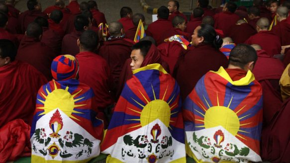 Exiled Tibetan Buddhist monks and nuns with a Tibetan flag wrapped ...