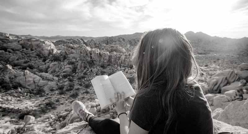 Girl reading on the mountain top