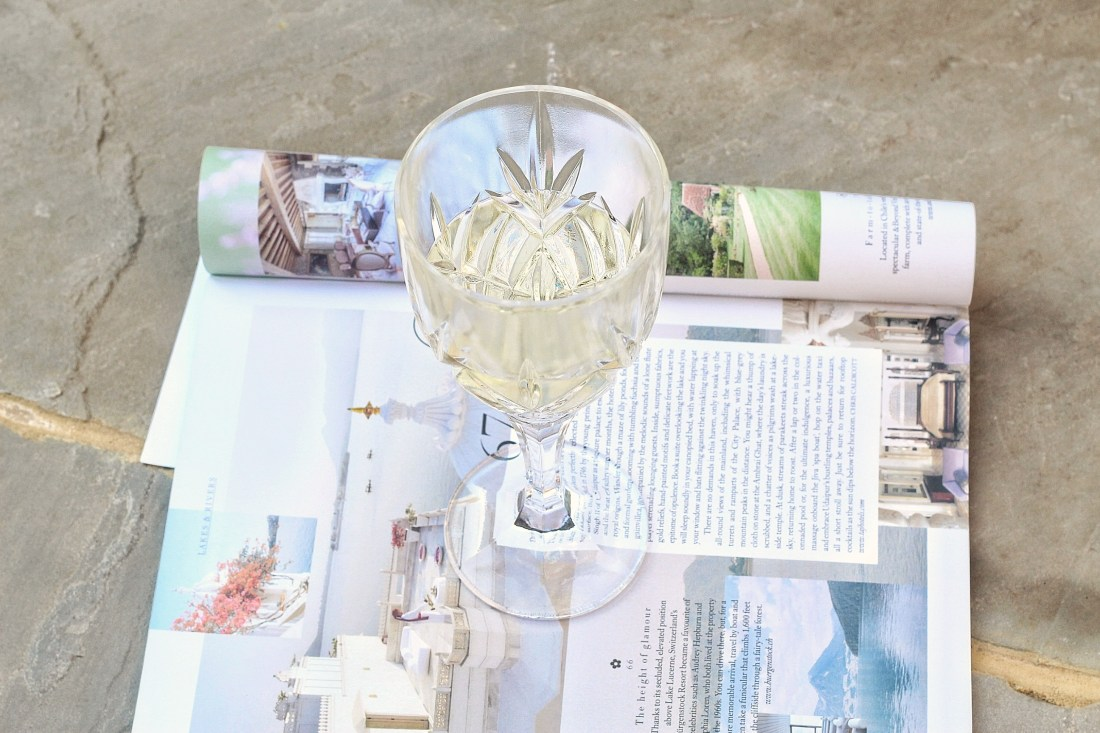 Glass of white wine with a magazine - blog post: how much should a guy spend on the first date