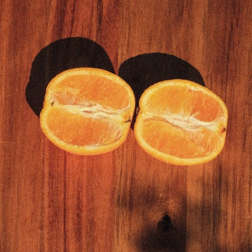 An orange cut in half on chopping board for blog on sex in a relationship