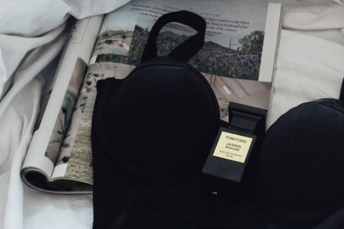 black bra with perfume bottle on bed for blog post on female orgasm