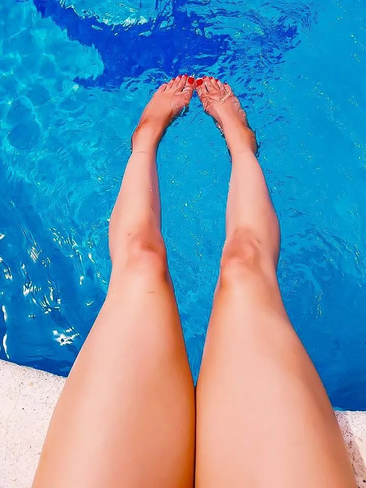 Image of legs in a pool for blog on skin tanning