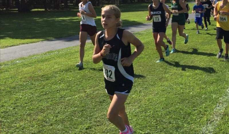 A member of the Summit girls Cross Country team leads a pack of runners down the field.