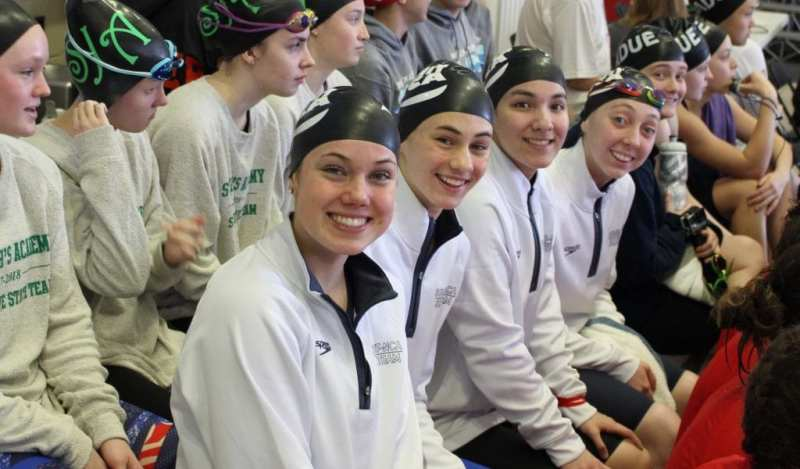 The Summit Preparatory School girls swim team smiles for a picture on the bench.