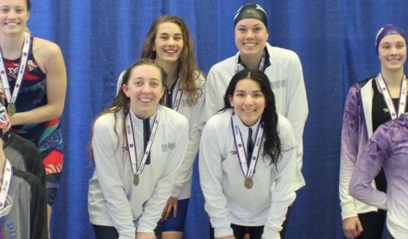 Four members of the girls Swim team pose for a picture with their medals after a swim meet.