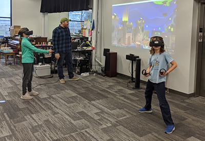 Two students at The Summit Preparatory school play a game together using a VR headset.