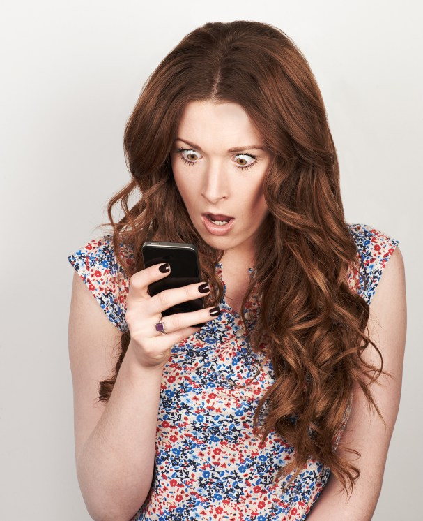 Woman on her phone looking shocked!