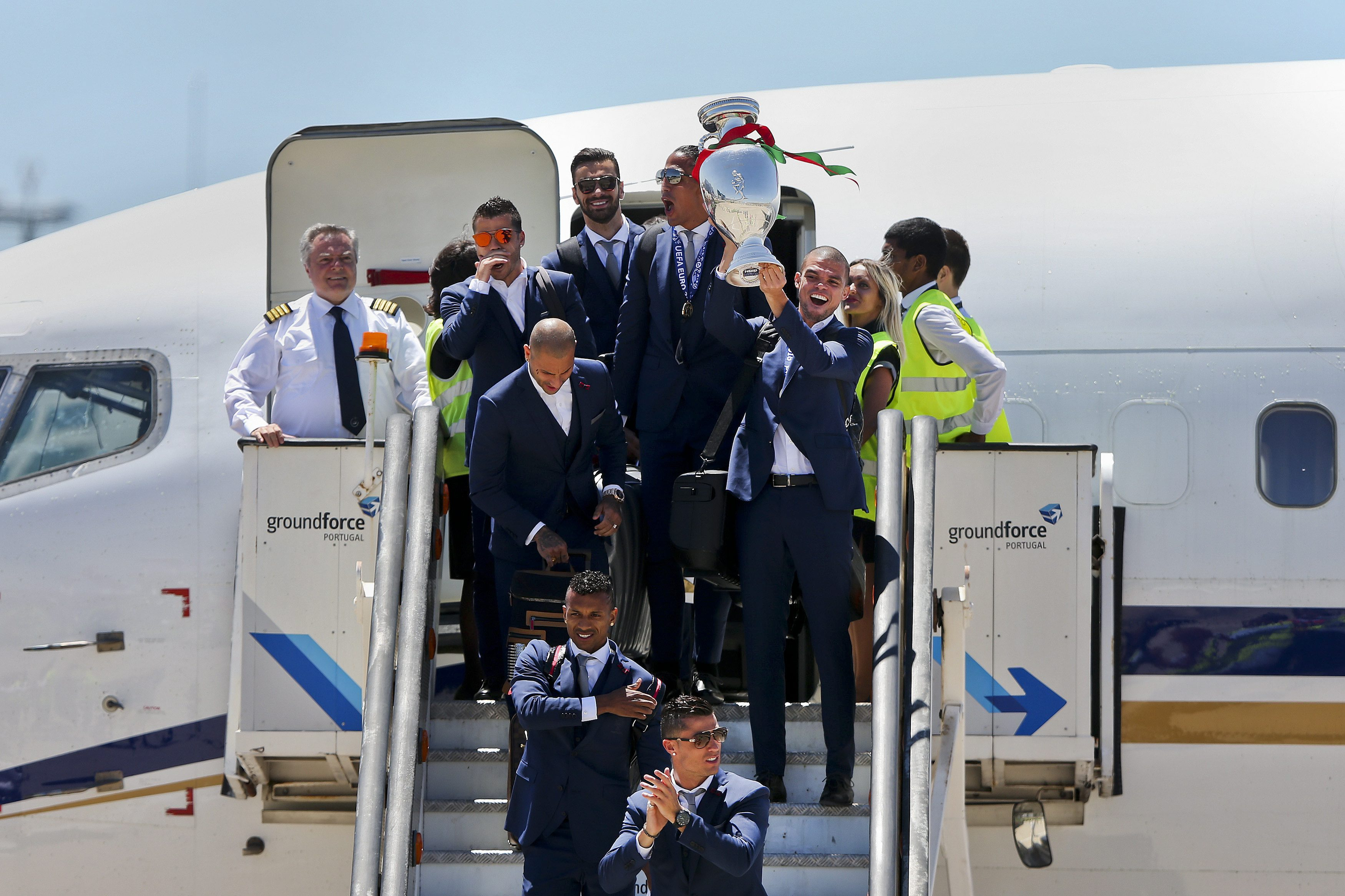 Defender Pepe lifts the cup as the victors leave the plane