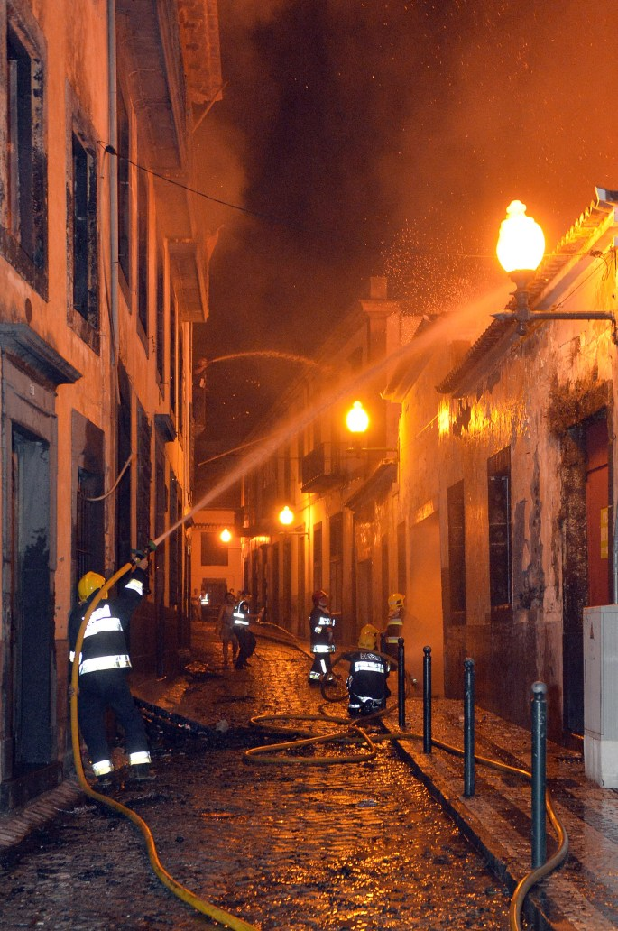 firefighters battle a fire that reached the old center of Funchal, the capital of Portugal's Madeira island