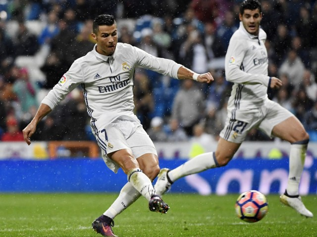 Real Madrid's Portuguese forward Cristiano Ronaldo (L) kicks the ball beside Real Madrid's forward Alvaro Morata during the Spanish league football match between Real Madrid CF and Athletic Club Bilbao at the Santiago Bernabeu stadium in Madrid on October 23, 2016. / AFP PHOTO / CURTO DE LA TORRECURTO DE LA TORRE/AFP/Getty Images
