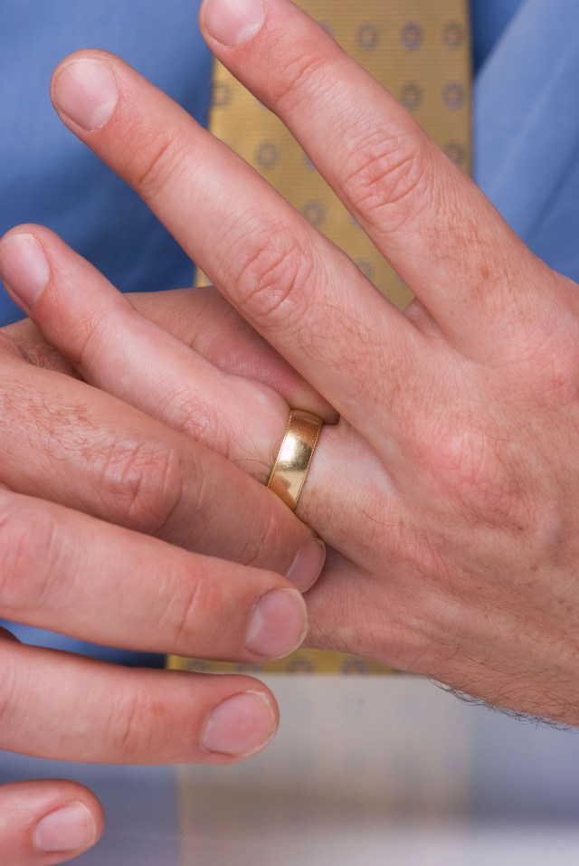 Close up of man?s hands with wedding ring on finger. Man touching wedding ring.