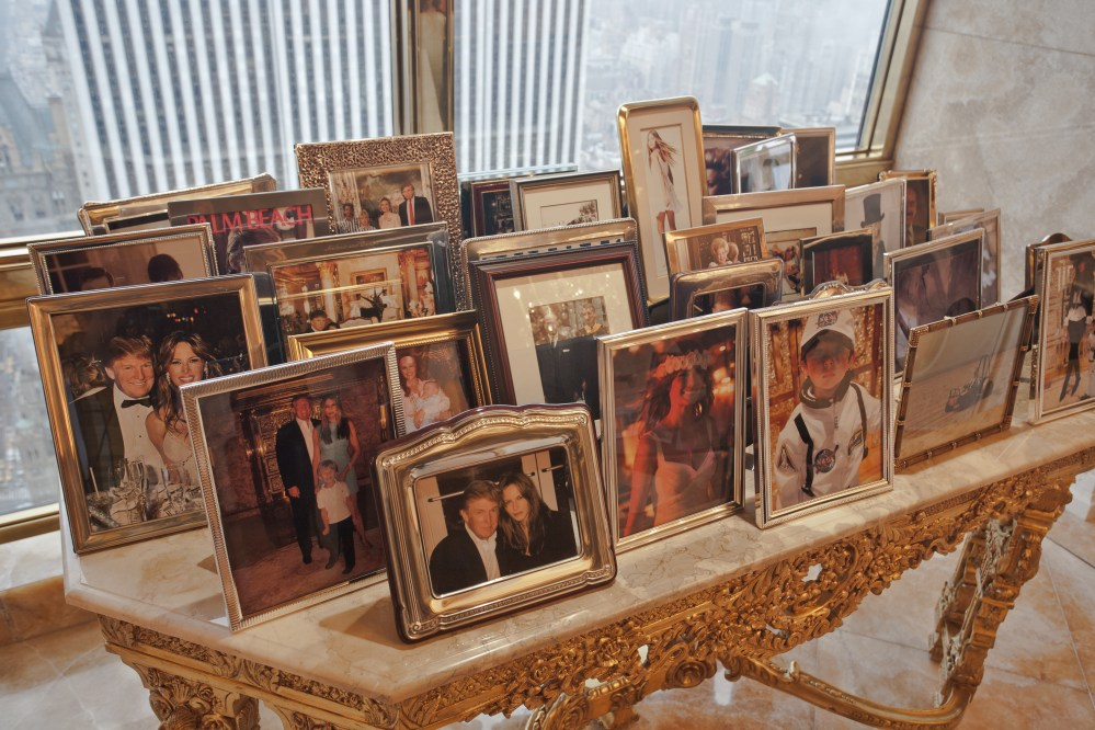 A collection of photographs of Trump's family, which include wife Melania, daughters Tiffany and Ivanka and sons Eric, Donald Jr and Barron, rest on this marble topped golden side table, partly masking the view of the New York skyline
