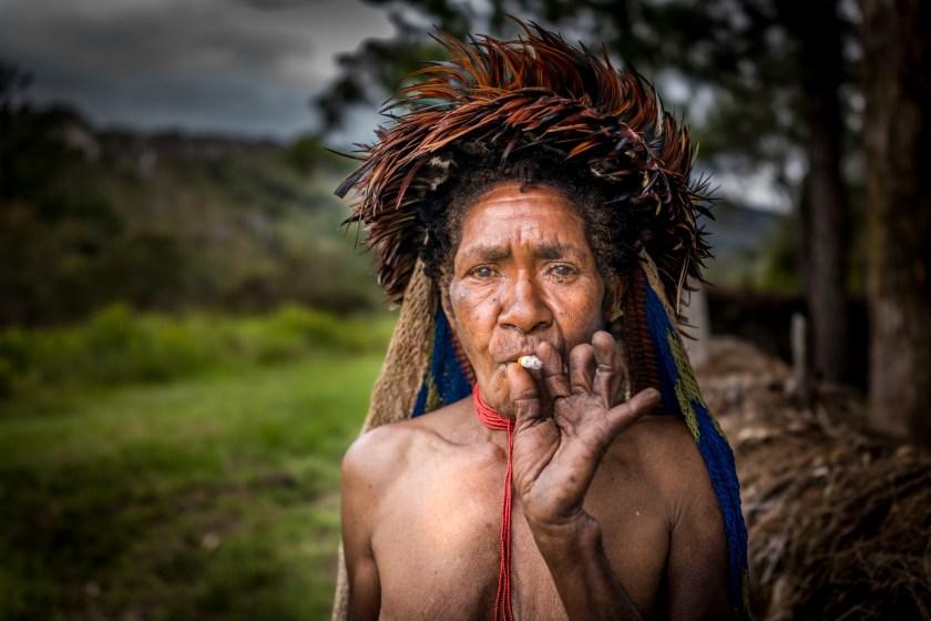 Tradisi yang menyakitkan ... Suku Dani mengisap rokok dan menunjukkan jarinya yang diamputasi
